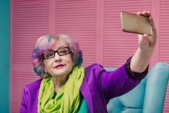Stilfull hög kvinna som använder den smarta telefonen Royaltyfria Bilder