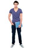 Stilfull högskolestudent som poserar med anteckningsboken royaltyfria bilder