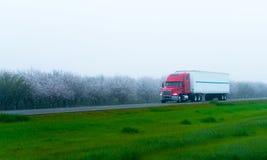 Stilfull halv lastbil och släp på huvudvägen med blommande träd Arkivfoto