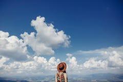 Stilfull handelsresandekvinna i hatten som ser himmel och berg höfter royaltyfri bild