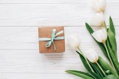 Stilfull hantverkgåvaask och tulpan på vit trälantlig baksida Royaltyfria Foton