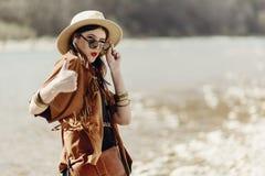 Stilfull hipsterbohokvinna som ler upp visningtummen, i sunglass Arkivbild