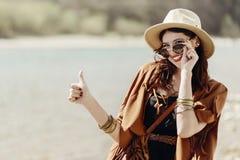 Stilfull hipsterbohokvinna som ler upp visningtummen, i sunglass Royaltyfri Foto