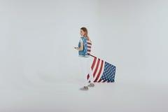 Stilfull hipsterflicka i den stora amerikanska patriotiska dräkten som rymmer oss flagga som isoleras på grå färger Royaltyfri Foto