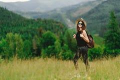 Stilfull hipsterkvinna med ryggsäcken och i hatt som ler på amazien Fotografering för Bildbyråer