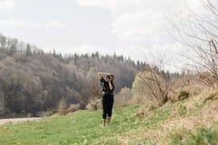 Stilfull hipsterkvinna som tar fotoet med den parallella foto-kameran i s Arkivbilder