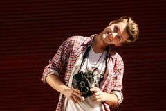 Stilfull hipsterman som rymmer den gamla retro parallella fotokameran och sm Arkivbild
