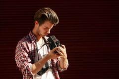 Stilfull hipsterman som rymmer den gamla retro parallella fotokameran på bac Royaltyfri Bild