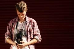 Stilfull hipsterman som rymmer den gamla retro parallella fotokameran på bac Royaltyfria Bilder