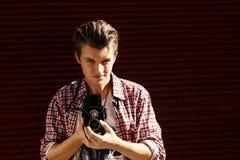 Stilfull hipsterman som rymmer den gamla retro parallella fotokameran på bac Arkivfoton