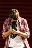 Stilfull hipsterman som rymmer den gamla retro parallella fotokameran på bac Royaltyfri Foto