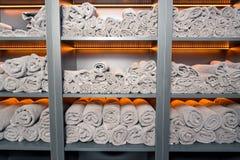 Stilfull hylla med vita handdukar, exponerat gult royaltyfria bilder