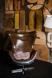 Stilfull inre i vindstil grå färger texturerade murbruk på väggträbokstäverna bekväm fåtölj som göras av brunt läder Nea fotografering för bildbyråer