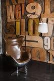 Stilfull inre i vindstil grå färger texturerade murbruk på väggträbokstäverna bekväm fåtölj som göras av brunt läder Nea royaltyfri fotografi