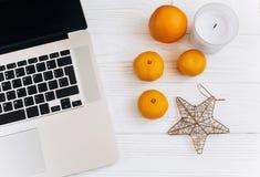 Stilfull jul sänker lekmanna- bärbar dator och apelsiner och guld- stjärna a Arkivbilder