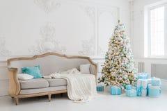 Stilfull jul som är inre med en elegant soffa Komforthem Framlägger gåvor under trädet i vardagsrum Arkivbild