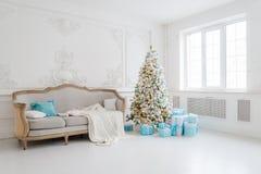 Stilfull jul som är inre med en elegant soffa Komforthem Framlägger gåvor under trädet i vardagsrum Royaltyfri Fotografi