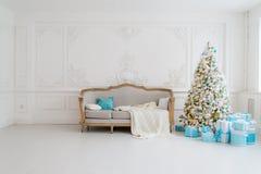 Stilfull jul som är inre med en elegant soffa Komforthem Framlägger gåvor under trädet i vardagsrum Royaltyfri Bild