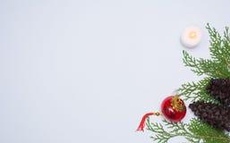 Stilfull julsammansättning granfilialer, kottar och julgarneringar på vit bakgrund Lekmanna- bästa sikt för lägenhet arkivfoto