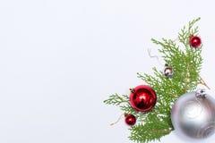Stilfull julsammansättning med granfilialer och garneringar på vit bakgrund Royaltyfria Foton