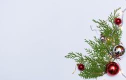 Stilfull julsammansättning med granfilialer och garneringar på vit bakgrund royaltyfri bild
