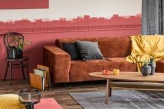 Stilfull kaffetabell framme av den bruna sammethörnsoffan i vardagsrum med ombreväggen royaltyfria bilder