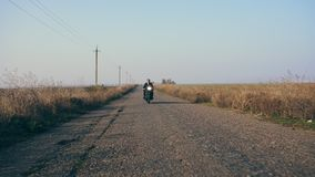 Stilfull kall ung man i solglasögon och läderomslaget som att närma sig, medan rida en motorcykel på en väg på en solig dag lager videofilmer