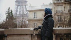 Stilfull kvinna i basker och laget som poserar att se omkring vid Eiffeltorn i Paris arkivfilmer