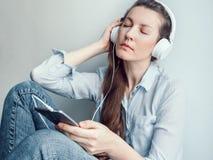 Stilfull kvinna i hörlurar som lyssnar till musik royaltyfri fotografi
