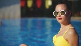 Stilfull kvinna i le för baddräkt som och för solglasögon sitter utanför i sommar lager videofilmer