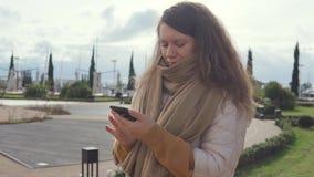 Stilfull kvinna med en utomhus- smartphone arkivfilmer