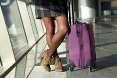 stilfull kvinna med ett resv?skaanseende p? f?nstret p? flygplatsen v?ntande flygplanflyg f?r handelsresande fotografering för bildbyråer