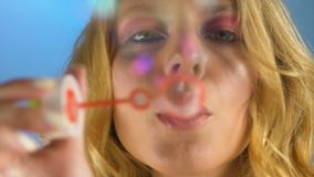 Stilfull kvinna som blåser såpbubblor, färgrika drömmar, lyckliga ögonblick och minnen stock video
