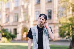 Stilfull le tonår för en student som lyssnar till musik- och knipahörlurar mot bakgrunden av universitetet Royaltyfri Foto