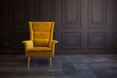 Stilfull ljus gul stol mot ett m?rkt - gr? v?gg royaltyfria bilder