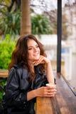 Stilfull lycklig ung kvinna i gatakafé Hon rymmer kaffe f?r att g? royaltyfria foton