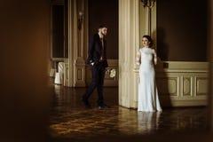 Stilfull lyxig brud och stilig elegant brudgum som poserar på lodisarna royaltyfria foton