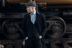 Stilfull man i den retro dräkten som poserar på bakgrund av järnvägen en Royaltyfri Fotografi