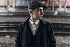 Stilfull man i den retro dräkten som poserar på bakgrund av järnvägen engelskt Royaltyfria Foton