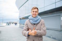 Stilfull man i ett grått lag med scraft på gatan arkivfoto
