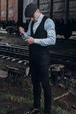 Stilfull man i retro blick som ler att posera på bakgrund av railwaen royaltyfria bilder