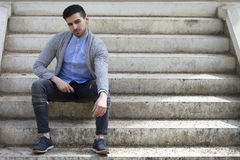 Stilfull man i tröja med skäggsammanträde på trappa royaltyfria bilder