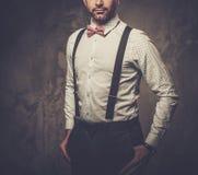 Stilfull man med bärande hängslen för fluga och posera på mörk bakgrund fotografering för bildbyråer
