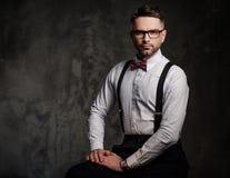 Stilfull man med bärande hängslen för fluga och posera på mörk bakgrund Royaltyfria Bilder