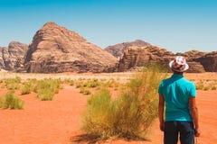 Stilfull man som bär den moderiktiga hatten och T-tröja som ser det fantastiska landskapet som tycker om liv Handelsresande frihe Arkivbilder