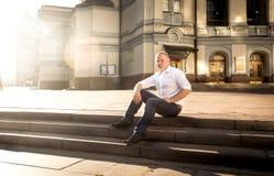Stilfull man som kopplar av på stentrappa på stor klassisk byggnad Royaltyfri Bild