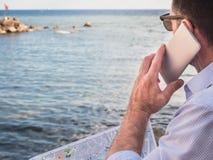 Stilfull man som rymmer i hans händer en telefon arkivbild