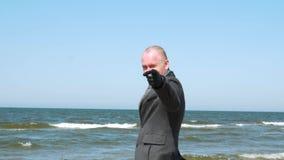 Stilfull man som visar dig tecknet, leende och att blinka för gest Elegant och s?ker ung aff?rsman p? stranden Aff?r lager videofilmer
