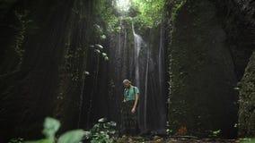 Stilfull manlig utforskare som vilar på en vagga i grotta nära en vattenfall bak honom Anseende för ung man i fjärd inom stock video