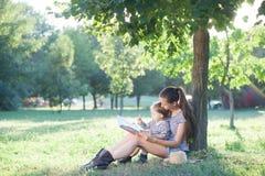 Stilfull moder- och litet barnläsebok på trädgården under sommargyckel royaltyfri foto